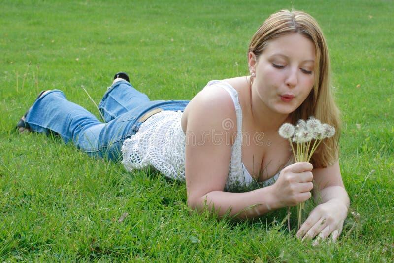 Jonge vrouwen blazende paardebloemen royalty-vrije stock afbeelding