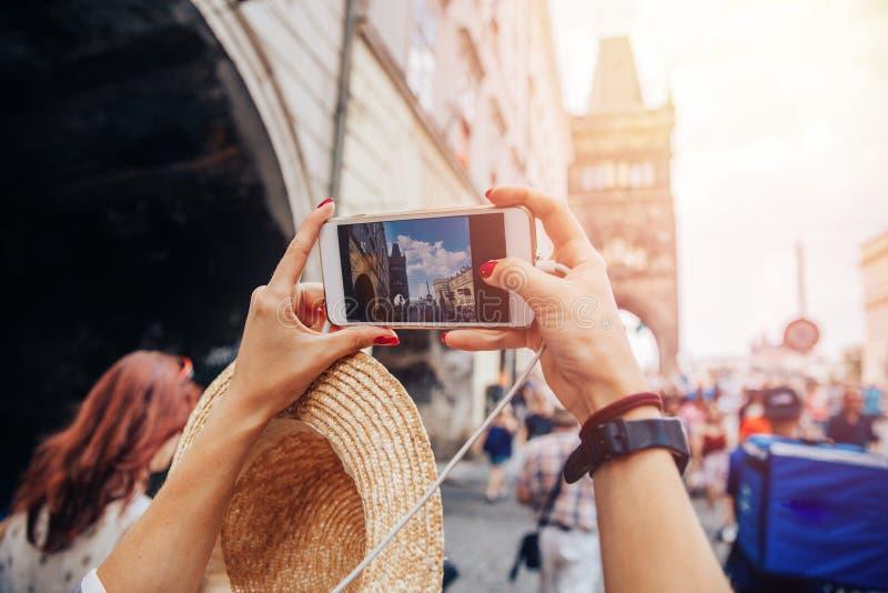 Jonge vrouwen blogger toerist die fotocamera op Charles Bridge in Praag, Tsjechische Republiek nemen Conceptenreis stock foto's