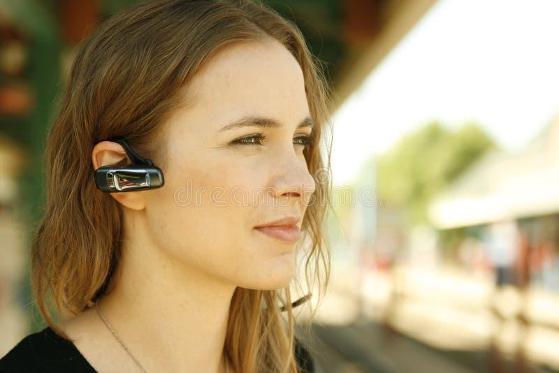 Jonge vrouwen bluetooth hoofdtelefoon stock fotografie