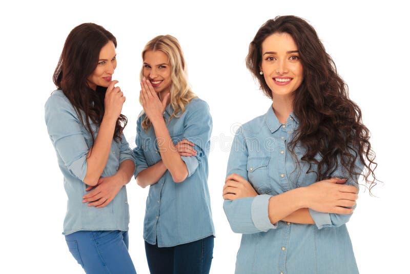 2 jonge vrouwen die achter de rug van hun leider spreken stock foto