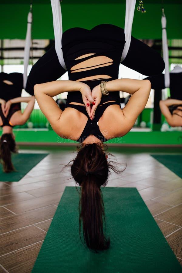 Jonge vrouwen die antigravity yogaoefeningen met een groep mensen maken de training van de de geschiktheidstrainer van de aerovli stock foto