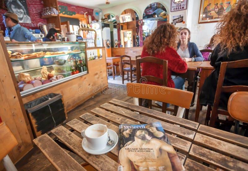 Jonge vrouwen die de bar van de koffiebinnenkant van de oude stad van Toscanië drinken royalty-vrije stock foto's