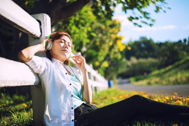 Jonge vrouwen die in de zomergras liggen met hoofdtelefoons die aan muziek luisteren stock afbeeldingen