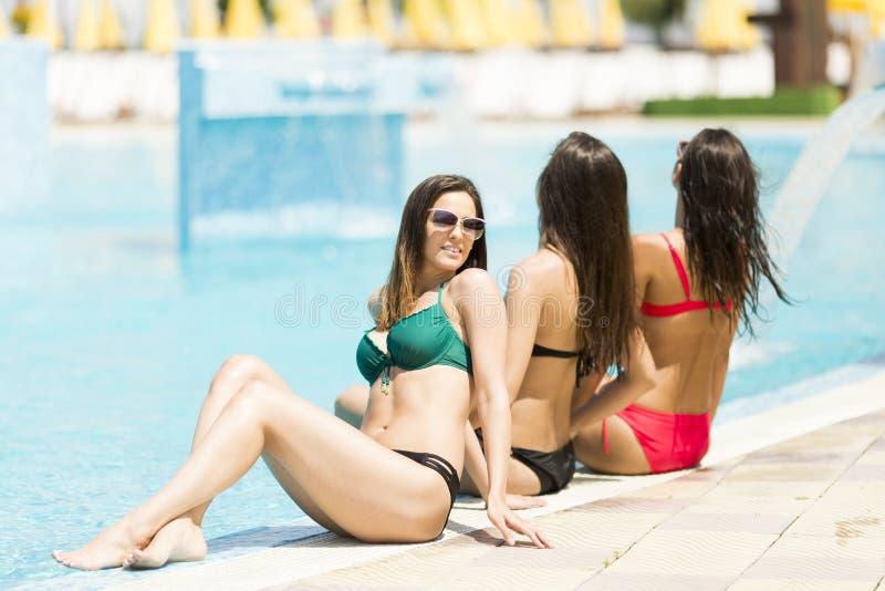 Jonge vrouwen die door de pool ontspannen royalty-vrije stock afbeeldingen