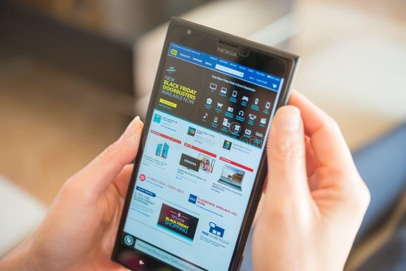 Jonge vrouwen die door mobiel op Bestbuy op Black Friday winkelen royalty-vrije stock afbeeldingen