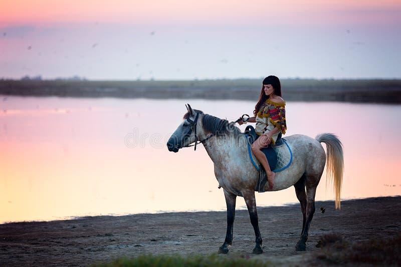 Jonge vrouwen die een paard berijden royalty-vrije stock afbeeldingen