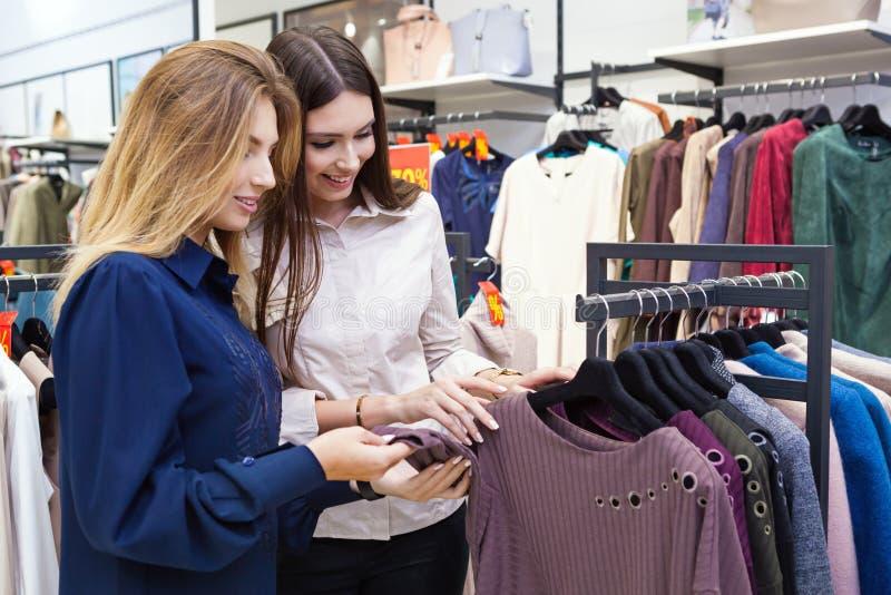 Jonge vrouwen die en wat kleding in een opslag winkelen bekijken stock foto's