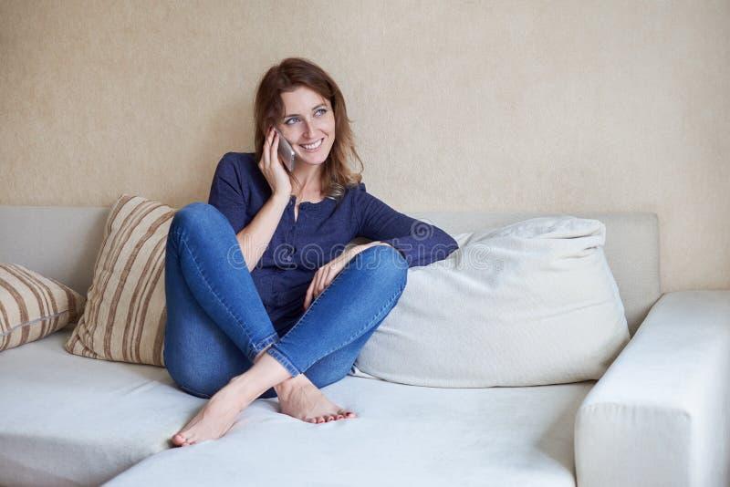 Jonge vrouwen die haar slimme telefoon op laag thuis in de woonkamer met behulp van royalty-vrije stock foto