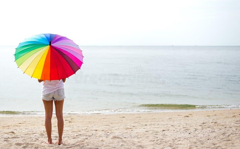 Jonge vrouwen die met paraplu springen en gelukkig op het strand stock fotografie