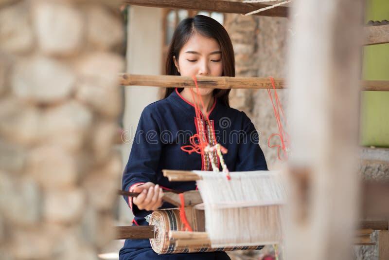 Jonge vrouwen die met traditionele Thaise wevende machine weven stock afbeelding