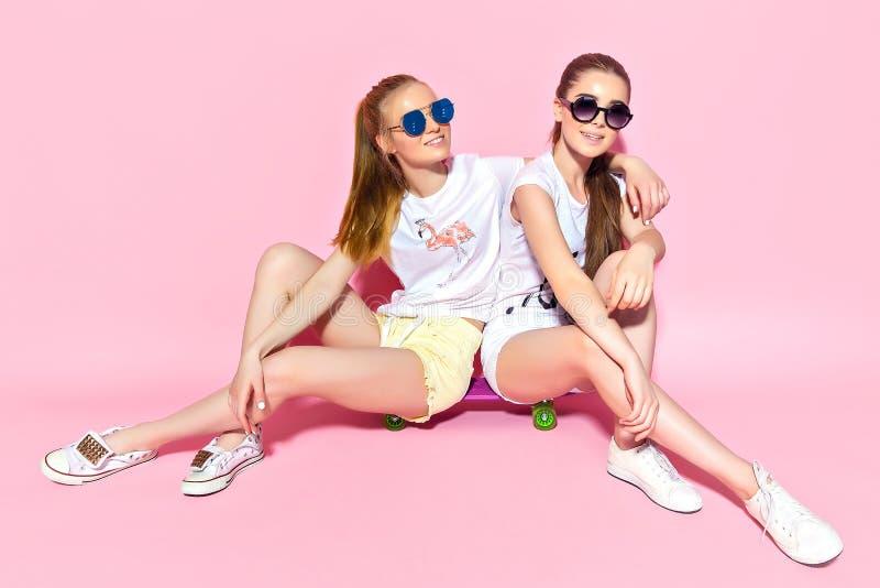 Jonge vrouwen die op skateboard zitten stock foto's