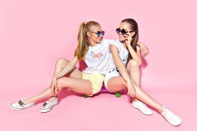 Jonge vrouwen die op skateboard zitten stock afbeelding