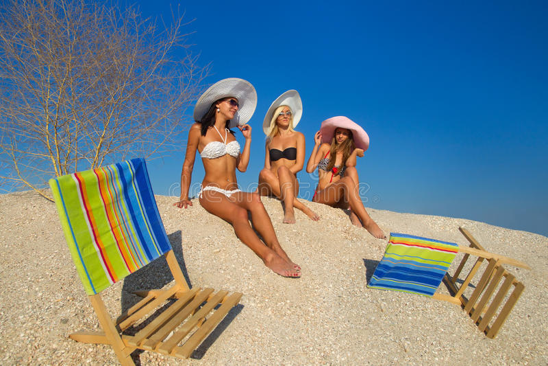 Jonge vrouwen die op strand ontspannen stock foto