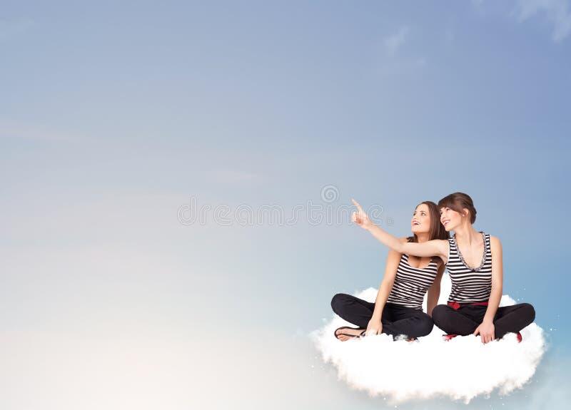 Jonge vrouwen die op wolk met exemplaarruimte zitten royalty-vrije stock afbeeldingen