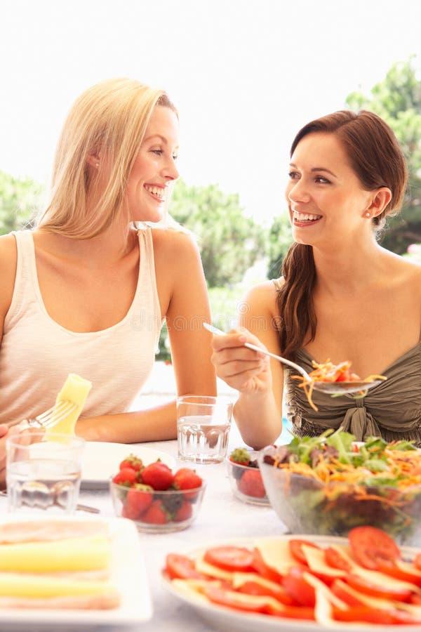 Jonge vrouwen die in openlucht eten royalty-vrije stock afbeelding