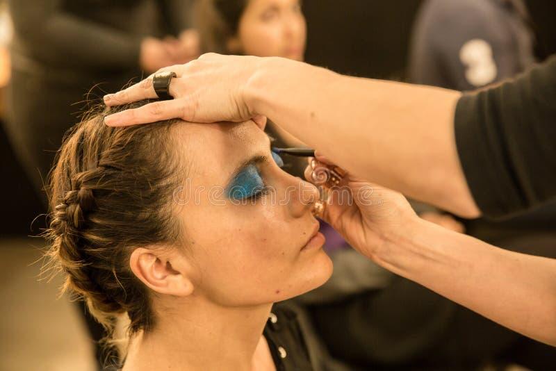 Jonge vrouwen die ouderwetse make-up doen, coulisse royalty-vrije stock afbeelding