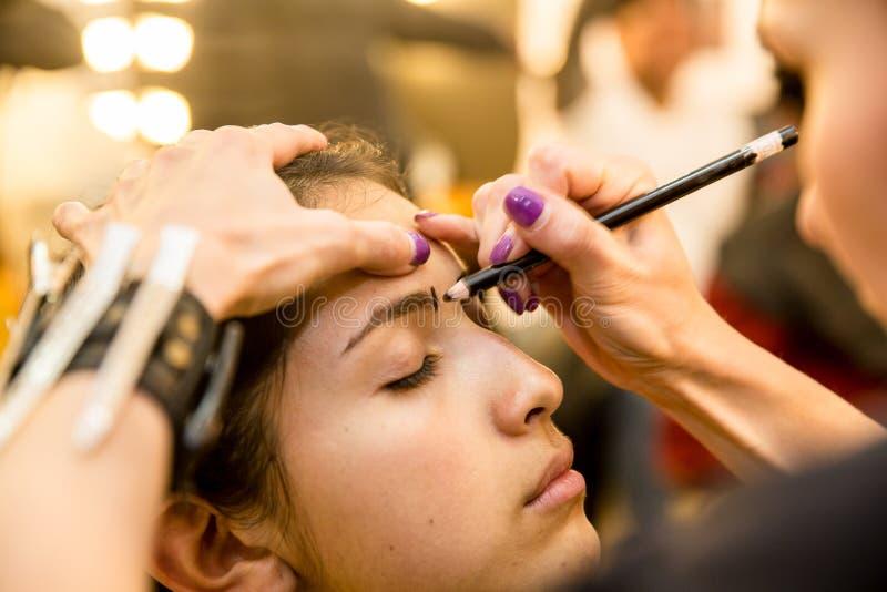 Jonge vrouwen die ouderwetse make-up doen, coulisse stock afbeeldingen