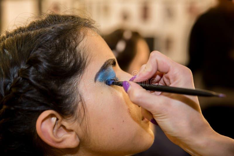 Jonge vrouwen die ouderwetse make-up doen, coulisse royalty-vrije stock afbeeldingen