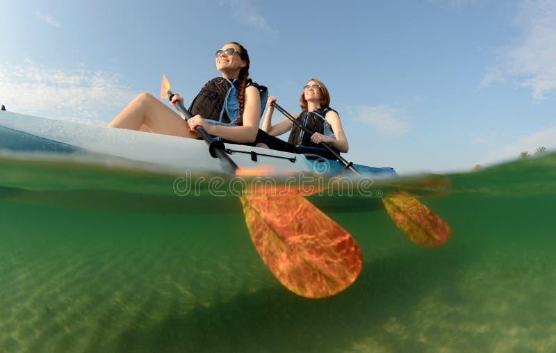 Jonge vrouwen die terwijl het kayaking in oceaan glimlachen royalty-vrije stock fotografie