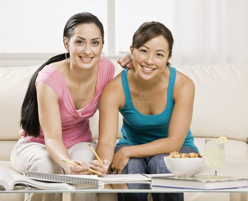 Jonge vrouwen die thuiswerk doen royalty-vrije stock afbeeldingen
