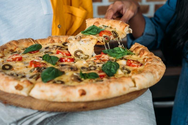 Jonge vrouwen die verse gebakken pizza samen eten stock afbeelding
