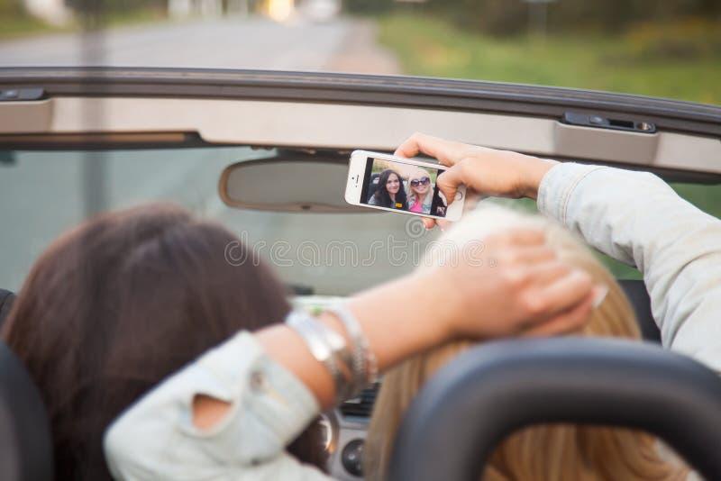 Jonge vrouwen die zelffoto in auto nemen stock fotografie