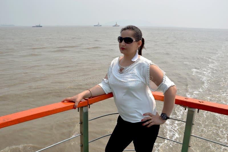 Jonge vrouwen die zich in schip het midden van zeewater bevinden royalty-vrije stock fotografie
