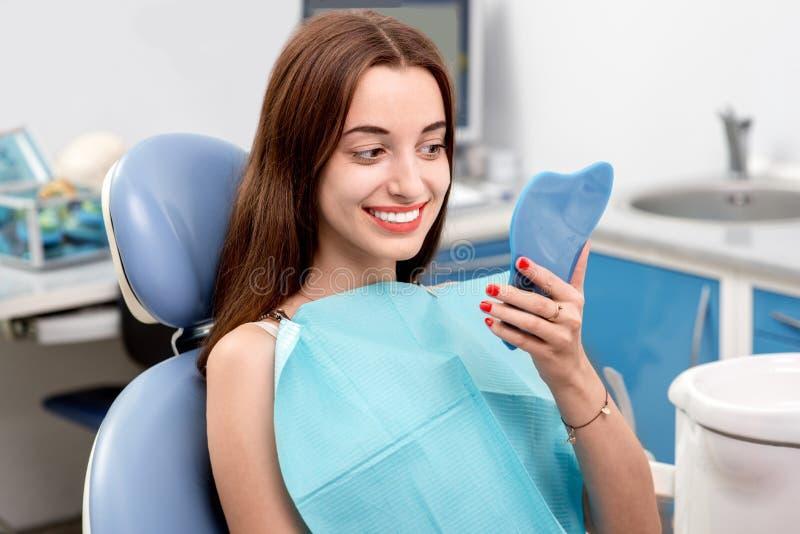 Jonge vrouwen geduldige bezoekende tandarts in tand stock afbeelding