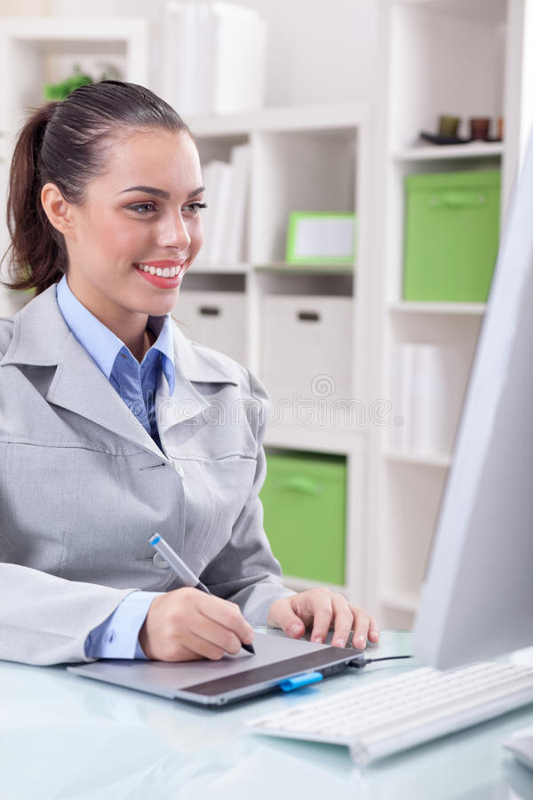 Jonge vrouwen grafische ontwerper die computer en grafische tablet gebruiken stock foto's