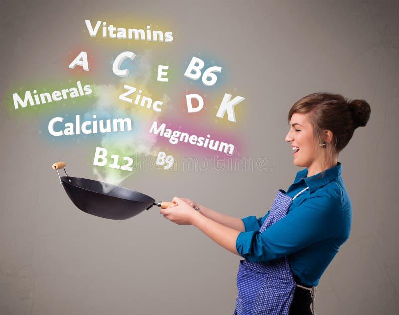 Jonge vrouwen kokende vitaminen en mineralen royalty-vrije stock afbeelding