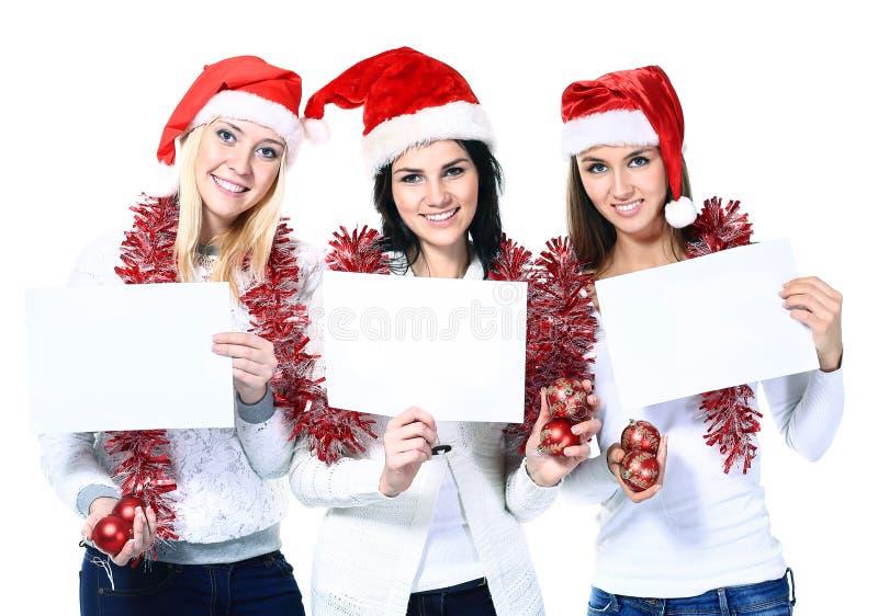 Jonge vrouwen in kostuum van Santa Claus met lege in hand kaarten stock foto's