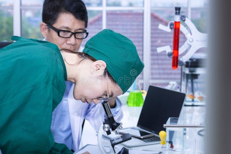 Jonge vrouwen medische student en onderzoekmedewerker met microscopen royalty-vrije stock foto