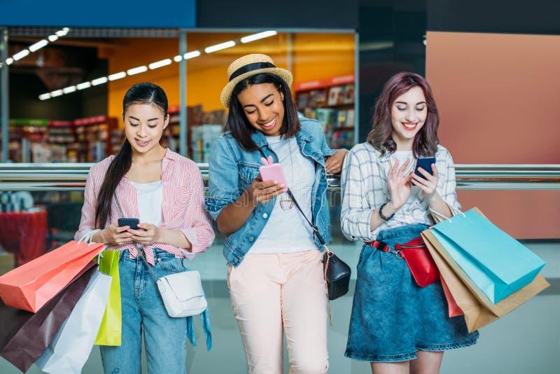 Jonge vrouwen met het winkelen zakken die smartphones, jong meisjes het winkelen concept gebruiken royalty-vrije stock foto's