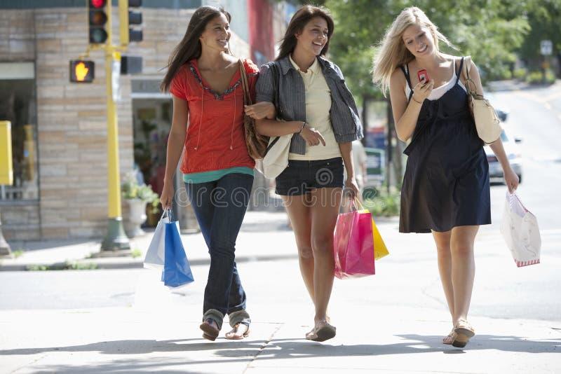 Jonge vrouwen op het winkelen reis het texting stock foto's