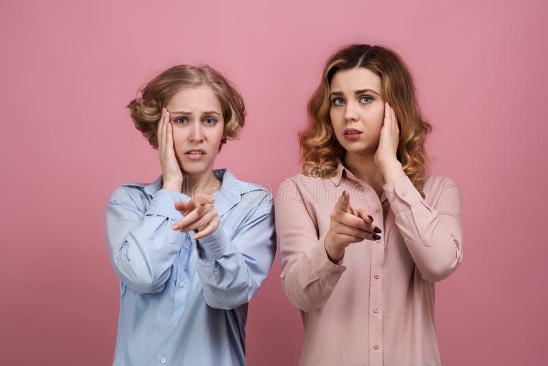 Jonge vrouwen in overhemden met een gestoorde uitdrukking die met zijn vinger op de camera en frown angstig richten stock afbeeldingen
