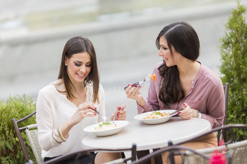 Jonge vrouwen in restaurant stock afbeeldingen