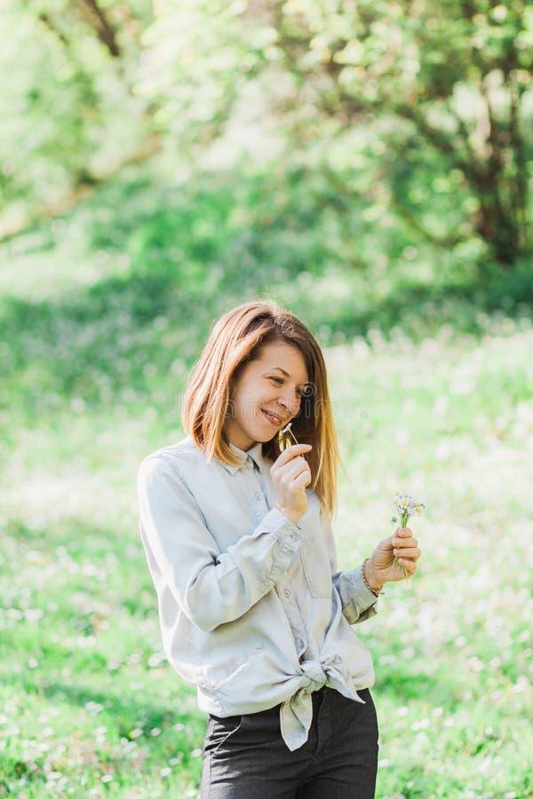 Jonge vrouwen ruikende bloemen buiten stock foto's