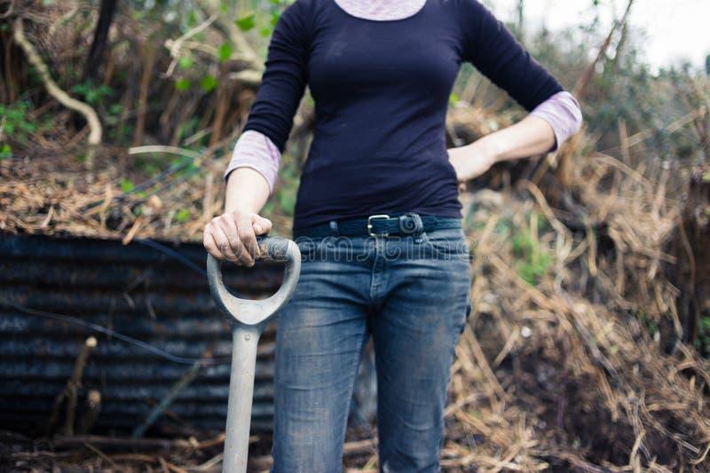 Jonge vrouwen rustende hand op spade stock foto's