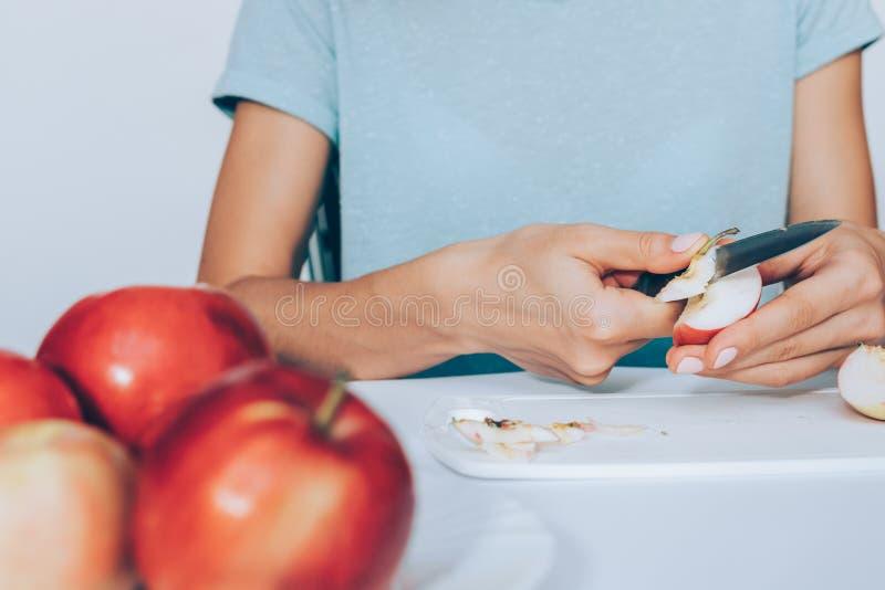 Jonge vrouwen scherpe vruchten op witte keuken stock fotografie