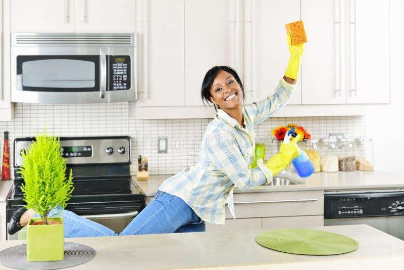 Jonge vrouwen schoonmakende keuken royalty-vrije stock fotografie