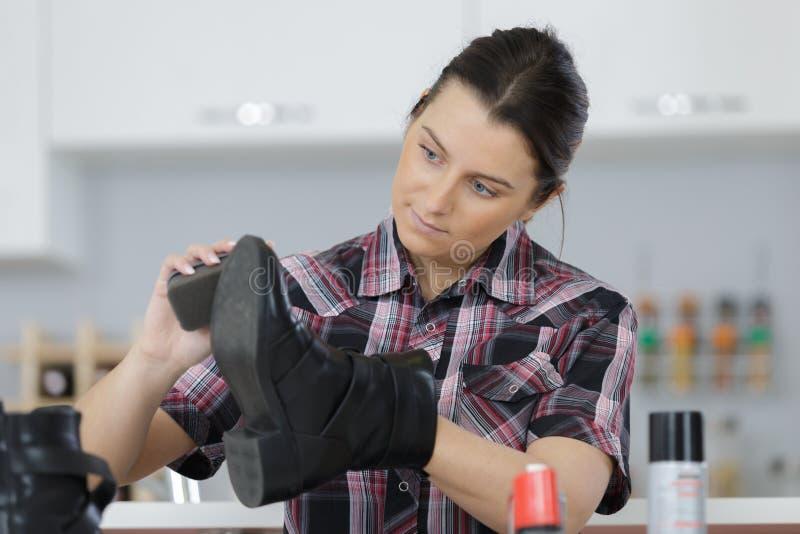 Jonge vrouwen schoonmakende schoenen in keuken royalty-vrije stock foto