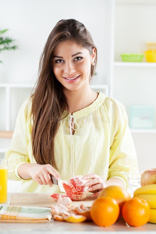 Jonge vrouwen snijdende Grapefruit stock foto's