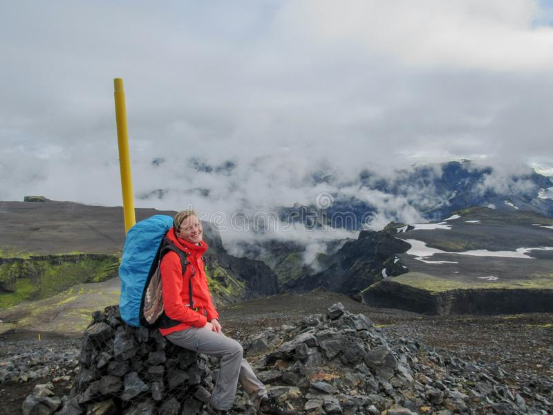 Jonge vrouwen wandelende avonturier in bergen met zware grote rugzak rustende zitting op steenhoop toneel adembenemend landschap stock afbeelding