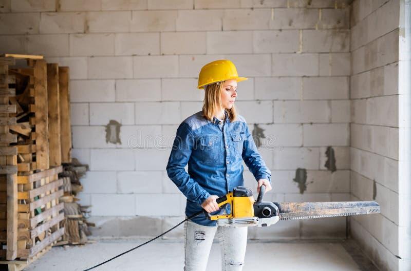 Jonge vrouwenarbeider met zaag op de bouwwerf stock afbeelding