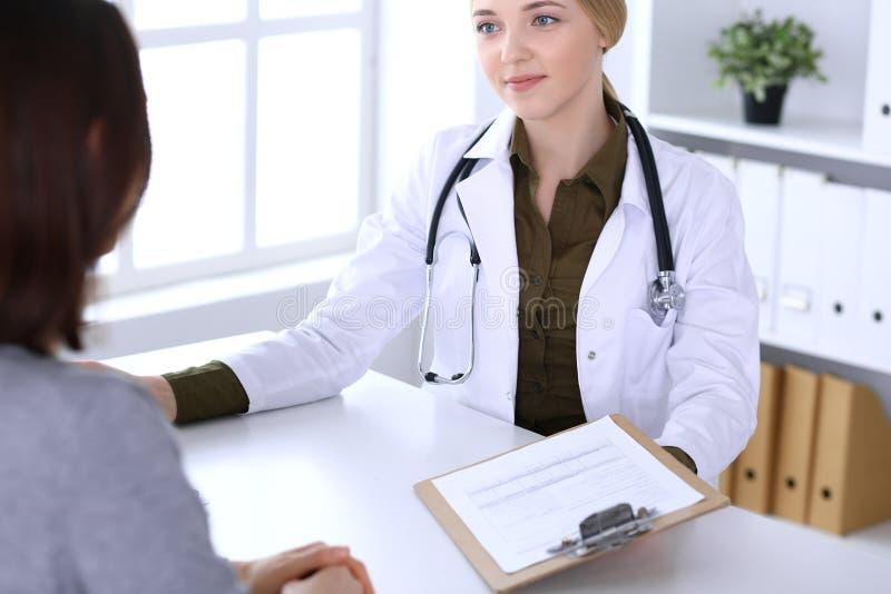 Jonge vrouwenarts en patiënt bij algemeen medisch onderzoek in het ziekenhuisbureau De kaki gekleurde blouse van therapeut kijkt  stock foto