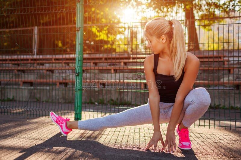 Jonge vrouwenatleet die alvorens op sportsground in de zomer te lopen opwarmen Actieve levensstijl royalty-vrije stock afbeelding
