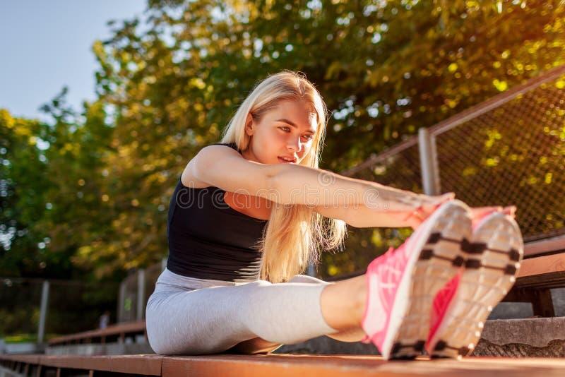Jonge vrouwenatleet die alvorens op sportsground in de zomer te lopen opwarmen Uitrekkend lichaam royalty-vrije stock afbeeldingen