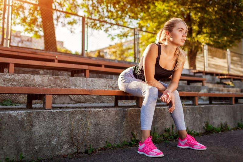 Jonge vrouwenatleet die rust na het lopen op sportsground in de zomer hebben royalty-vrije stock fotografie