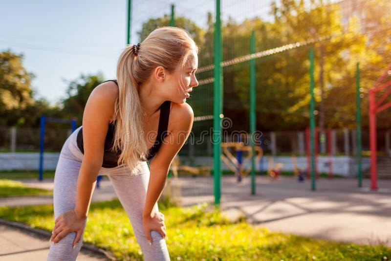 Jonge vrouwenatleet die rust na het lopen op sportsground in de zomer hebben stock afbeelding