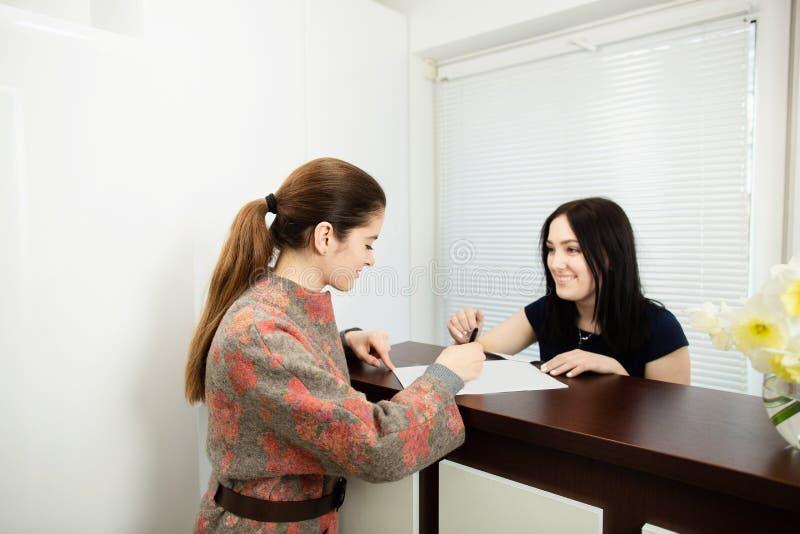 Jonge vrouwenbeheerder in een tandkliniek in de werkplaats Toelating van de cli?nt stock fotografie